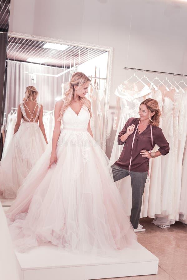Tailleur féminin professionnel regardant la jeune mariée image libre de droits