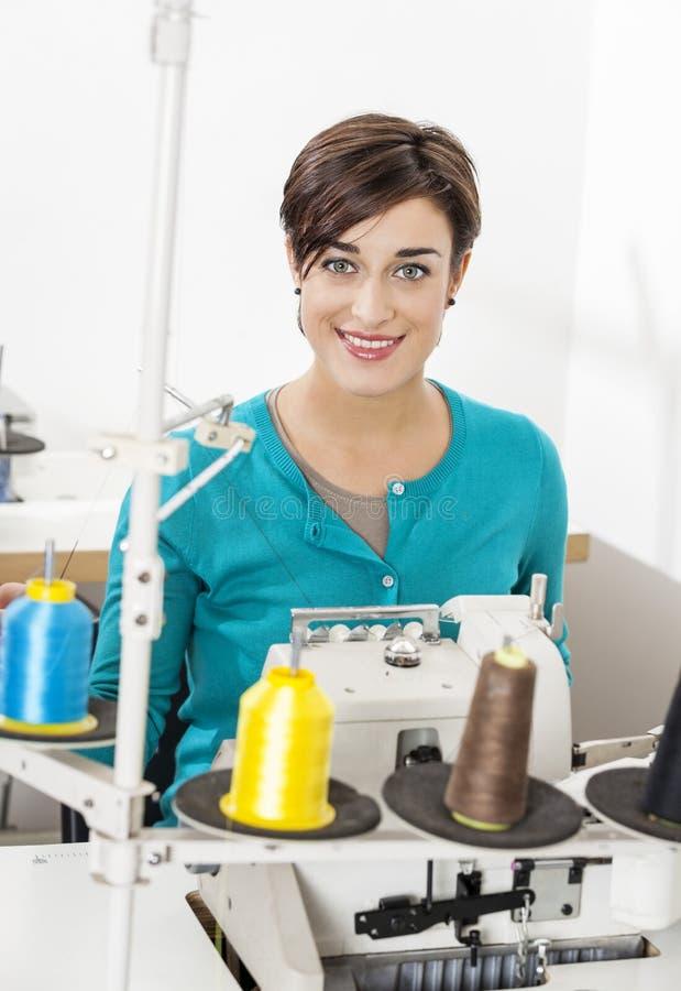 Tailleur heureux Sitting At Workbench dans l'usine de couture images stock