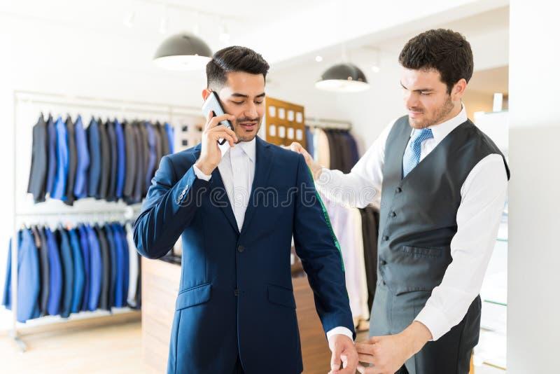 Tailleur Measuring Arm Length de client occupé image stock