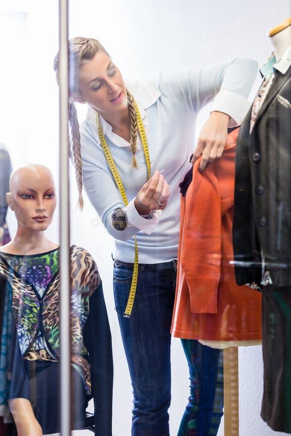 Tailleur montrant la mode dans la fenêtre de boutique photographie stock libre de droits