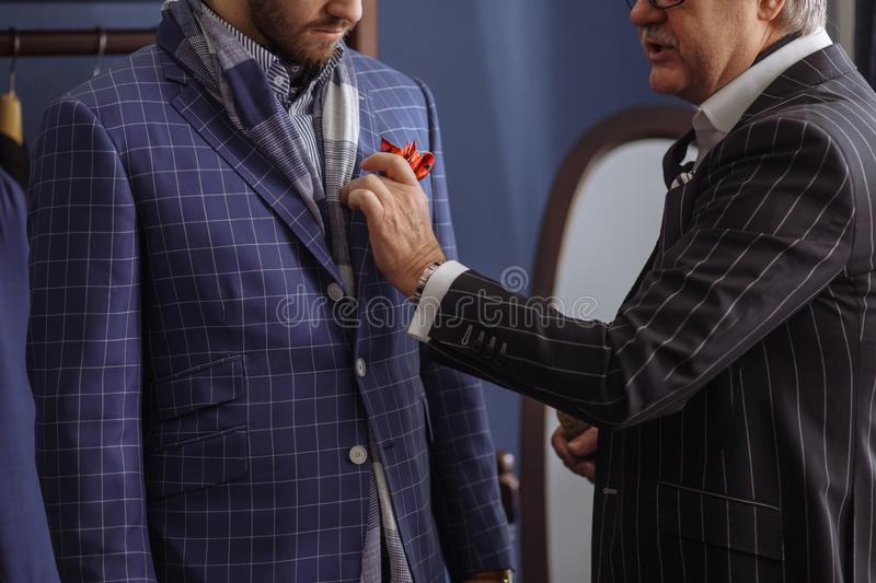 Tailor with client in atelier. Sewing custom made suit royalty free stock photography