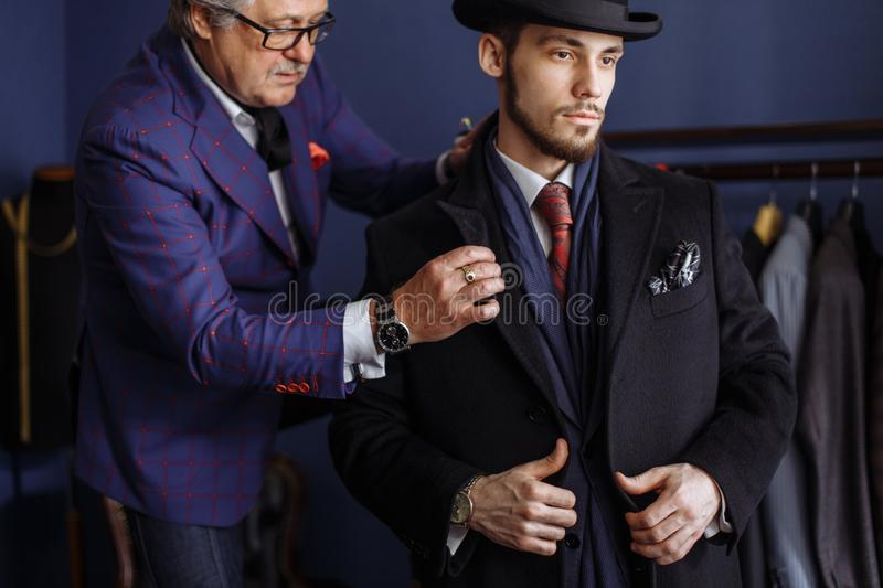 Tailor with client in atelier. Sewing custom made suit royalty free stock photos