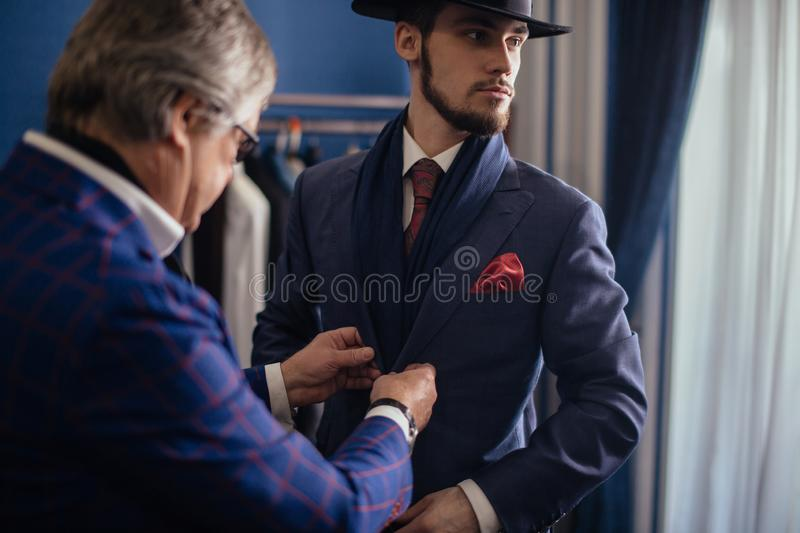 Tailor with client in atelier. Sewing custom made suit stock photography