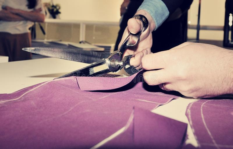 Tailor cutting fabric for bespoke suit stock images