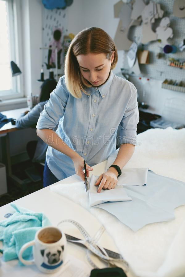 Tailor Cutting Fabric With Scissors In Atelier stock photography