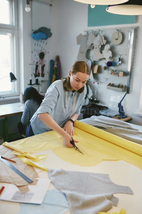 Tailor Cutting Fabric With Scissors In Atelier stock photos