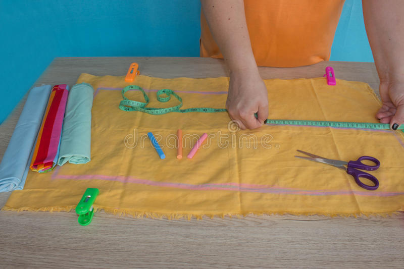Tailor cutting fabric using large scissors or shears as he follows the chalk markings of the pattern, close up of his hands stock photo