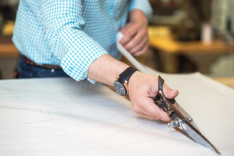 Tailor cutting out the marked pattern on fabric with large scissors on the workbench in his shop, close up view of his stock photo