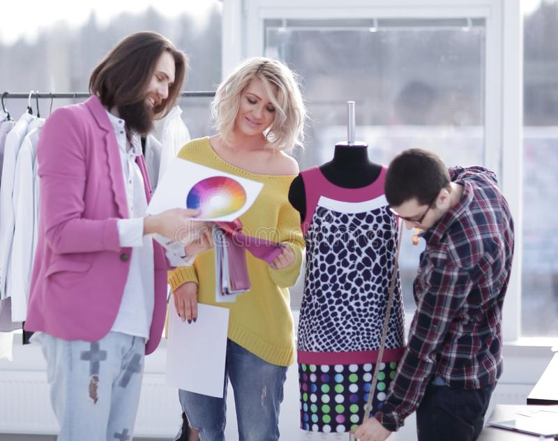Tailor and designers discussing new fabric patterns in creative workshop stock photography