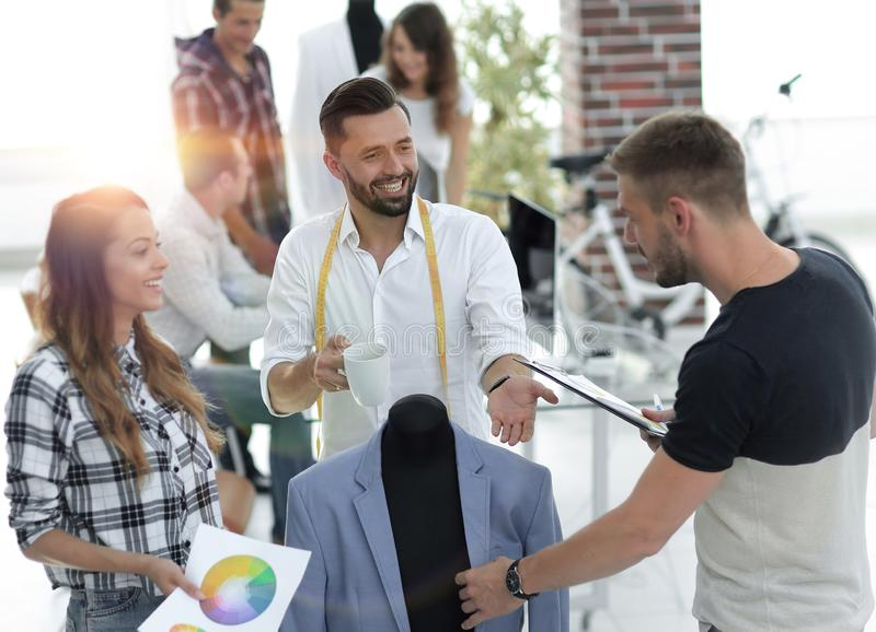 Tailor and designers to discuss men`s suit stock images