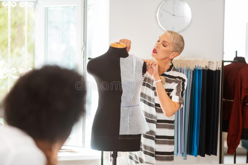 Professional fashion designer measuring the length of shoulder royalty free stock photos