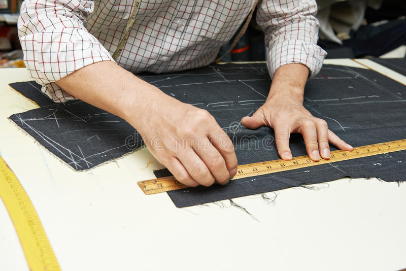 Tailor hands at works. Tailor hands working with measure bar
