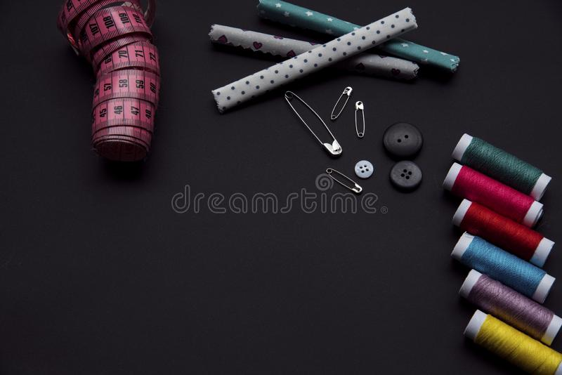 Tailor materials on the balck background. With pink measure. There is space for advertisement stock images