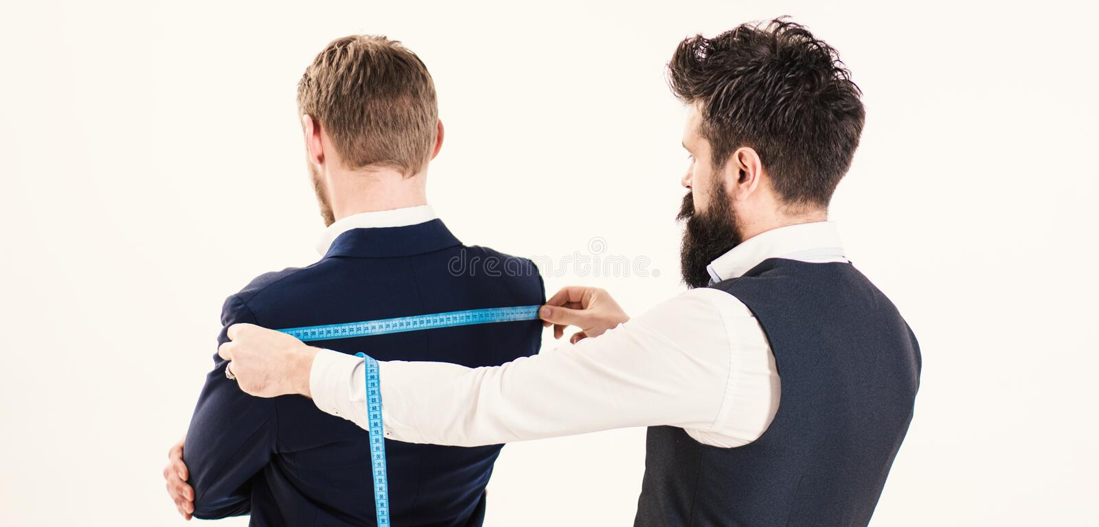 Tailor measuring client for custom made garment. royalty free stock photos
