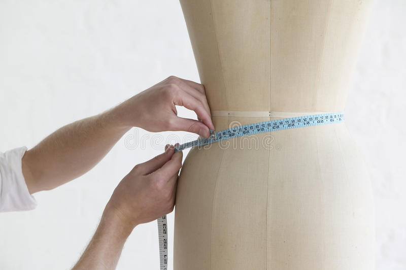 Tailor Measuring Mannequin's Waist In Studio royalty free stock photo