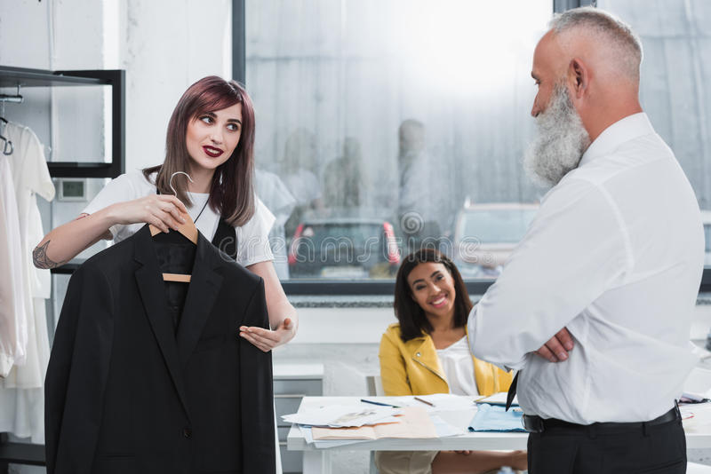 Tailor proposing senior man to try on suit jacket indoors. Caring tailor proposing senior men to try on suit jacket indoors royalty free stock image
