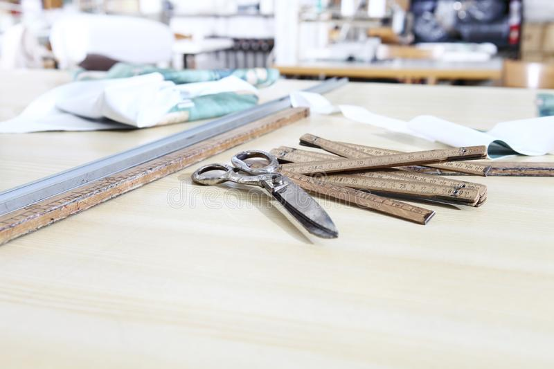 Tailor`s tools, old scissors, wooden meter and ruler on the sartorial work table royalty free stock photo