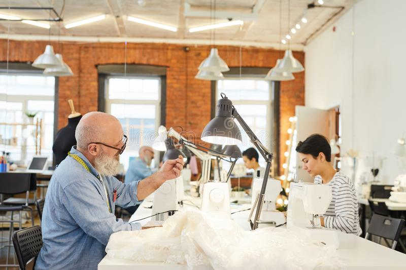 Tailor sewing in workshop. Mature self-employed tailor sitting by workplace while sewing white dress for new seasonal collection in workshop stock images