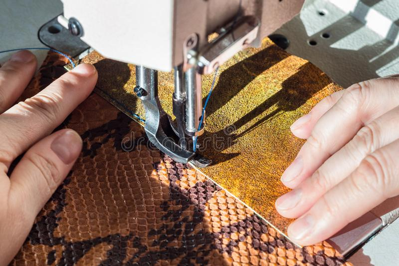 Tailor sews leather pieces on sewing machine stock photography