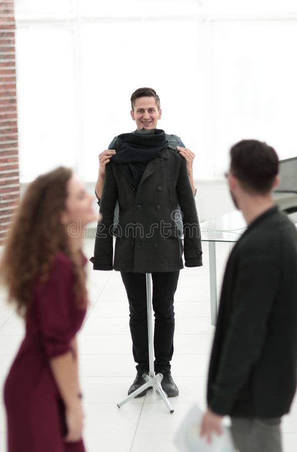Tailor , showing a jacket to a group of designers royalty free stock image