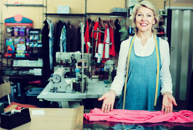 Tailor standing in sewing workshop. Cheerful mature woman tailor standing in sewing workshop stock image