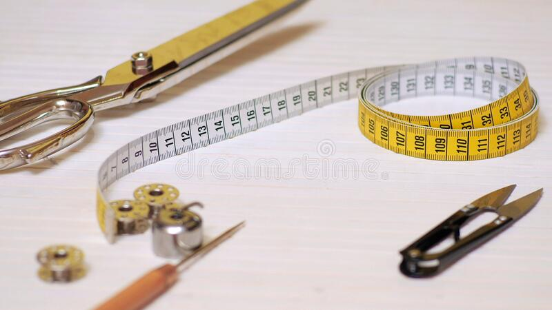 Tailor tools isolated on wooden background. Scissors, needle, Tailoring Meter, hand royalty free stock photography
