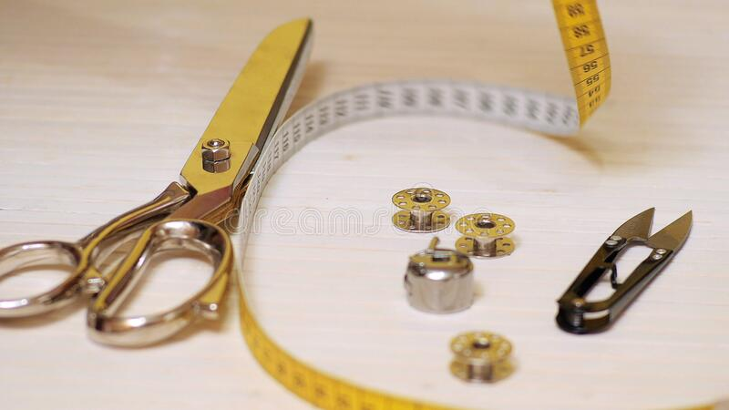 Tailor tools isolated on wooden background. Scissors, needle, Tailoring Meter, hand stock photo