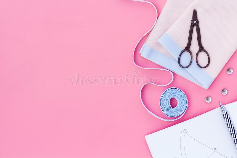 Tailor work place with thread, scissors, fabric. Sewing as hobby. Pink background top view space for text royalty free stock image