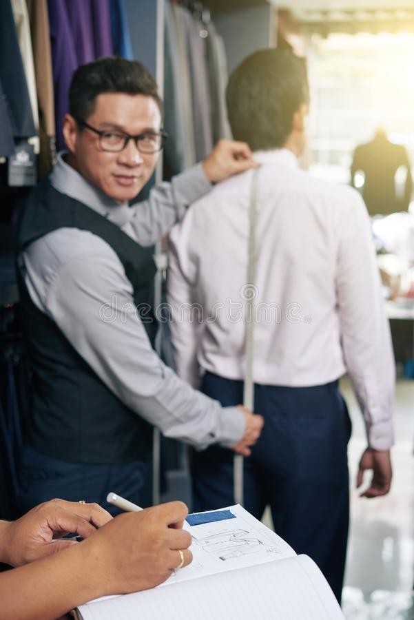Tailor working with client stock images