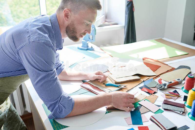 Tailor working with leather. Serious professional master working at his workplace working with pattern of leather textile stock image
