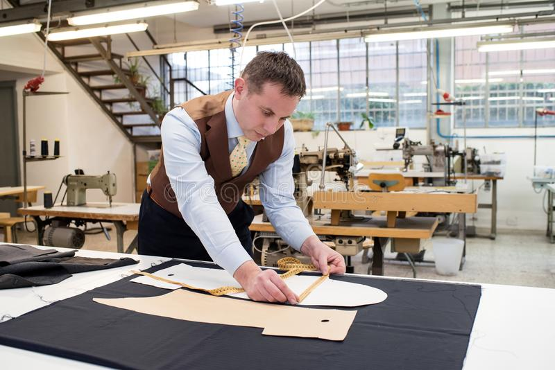 Tailor working with paper patterns on new jacket royalty free stock image