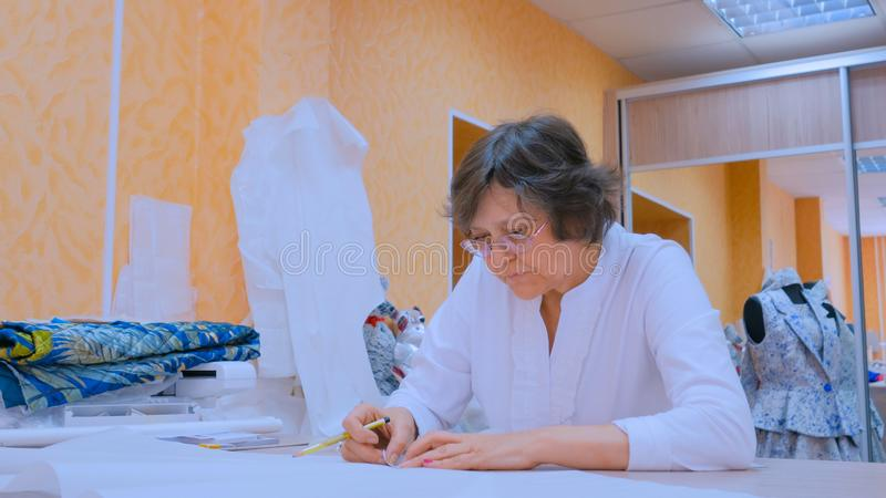 Tailor working with pattern of new couture collection stock image