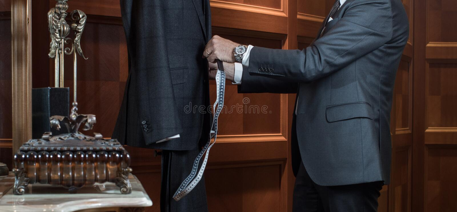 The tailor works with the dummy measuring suit stock photo
