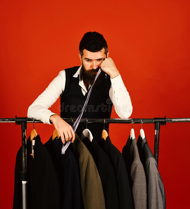 Tailoring and lack of work concept. Man with beard by clothes rack, Designer leans on hand near custom jackets. royalty free stock photos