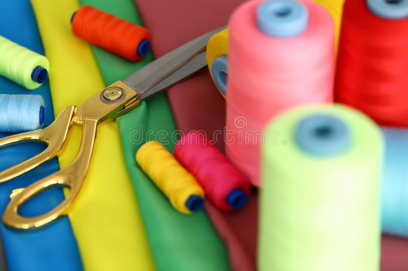 Tailors equipment for work. Focus on needle tools for creating fashionable clothes. Scissors lying on table near sewing bobbins standing on fabric swatches royalty free stock photography