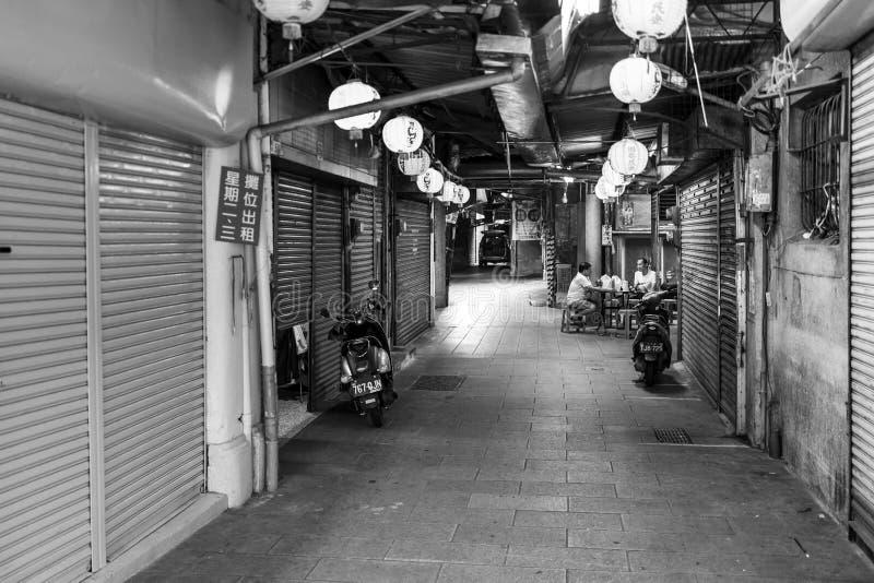 Tainan, Taïwan - 25 septembre 2018 : Deux hommes s'asseyant entre les boutiques fermées à Tainan photographie stock