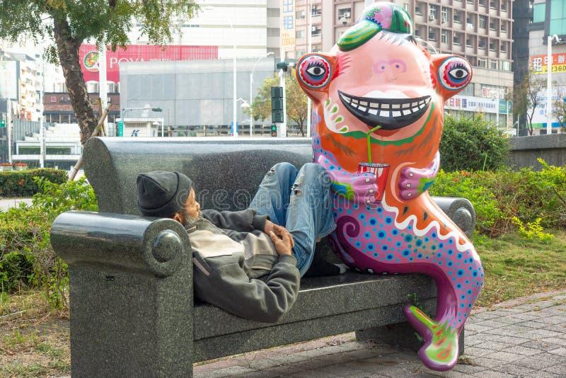 Tainan/Taiwan-13 03 2018: A estátua engraçada e o homem desabrigado de sono foto de stock
