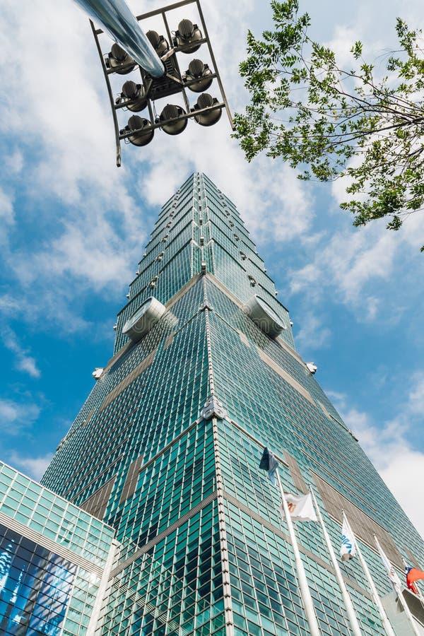 Taipeh 101 gebouwen met boom vertakt zich en de bouw lichte post van onderaan met heldere blauwe hemel en wolk in Taipeh, Taiwan stock fotografie