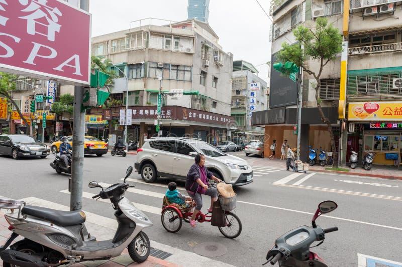 TAIPEH, TAIWAN - 30. NOVEMBER 2016: Taipeh-Straße in einer von Vorort, Bezirk Frau auf Fahrrad stockfotografie