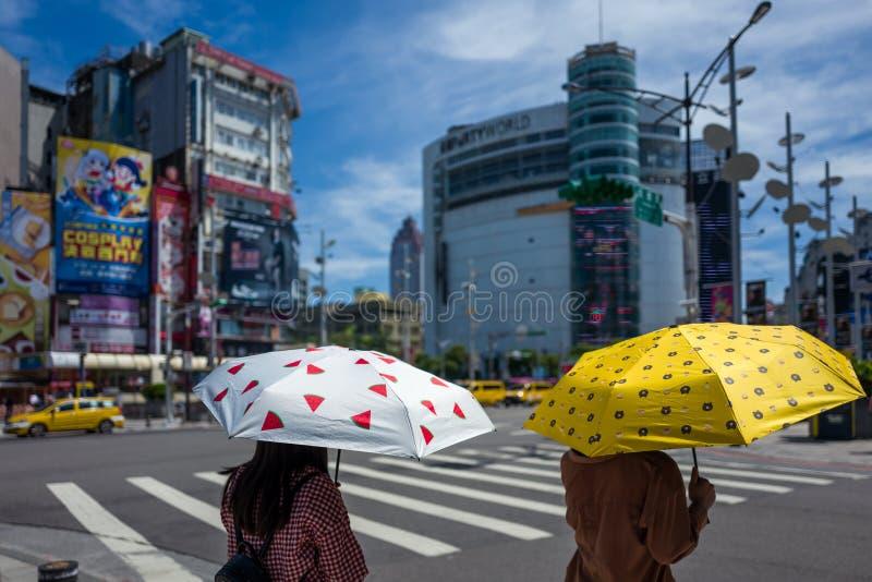 Taipeh, Taiwan - September 18, 2018: Twee meisjes met paraplu's beschermen zich tegen de zon stock afbeelding