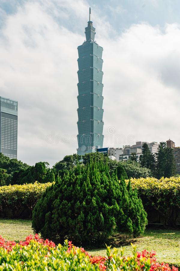 Taipei 101 building with tree bushes in foreground with bright blue sky and cloud in Taipei, Taiwan royalty free stock image