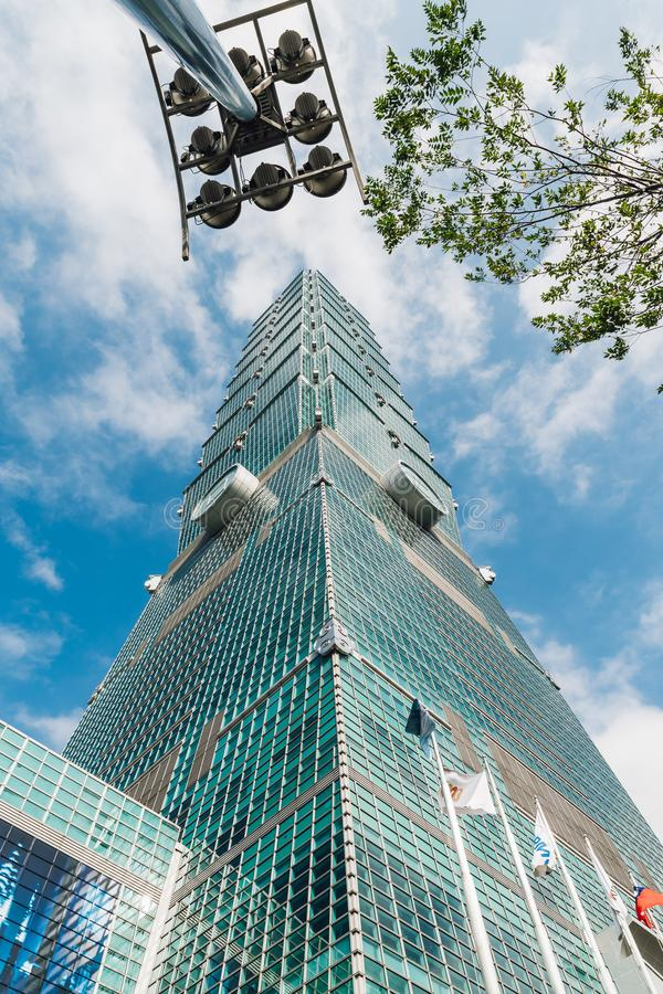 Taipei 101 buildings with tree branches and building light post from below with bright blue sky and cloud in Taipei, Taiwan stock photography