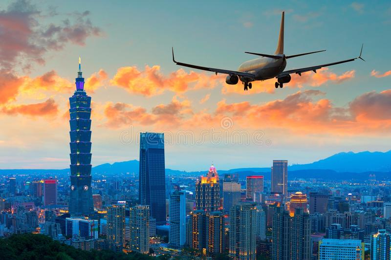 Passenger jet airliner plane arriving or departing Taipei, Taiwan. Taipei skyline with a commercial passenger jet airliner plane arriving or departing royalty free stock photography