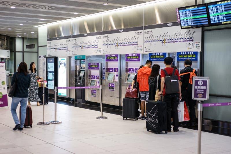 Taipei, TAIWAN - 1º de outubro de 2017: Os viajantes compram um bilhete de trem da máquina de venda automática do cartão no aerop imagens de stock