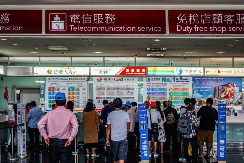 Taipei, TAIWAN - 1º de outubro de 2017: Os viajantes compram um sim móvel dos sevices do contador da telecomunicação no aeroporto imagem de stock royalty free