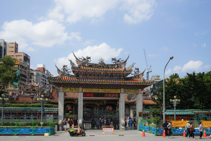 Taipei Taiwan - April 19, 2018: Folk som går och att trafikera framme av porten av LONGSHAN-templet royaltyfri foto