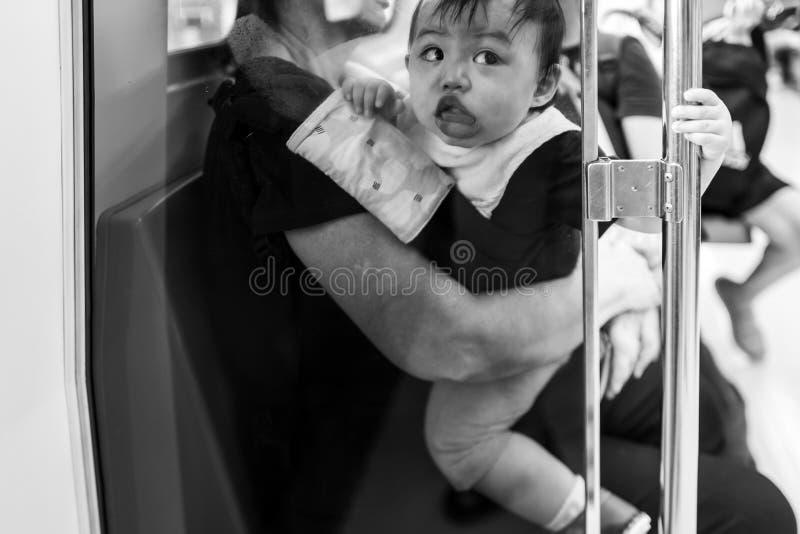 Taipei, Taiwan - 19 de setembro de 2018: Criança bonito que põe o boca do ` s sobre uma placa de vidro no MRT fotografia de stock