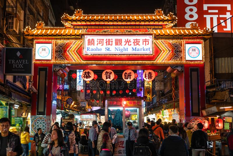 Street view of Raohe Street food Night Market full of people and entrance gate in Taipei Taiwan royalty free stock image