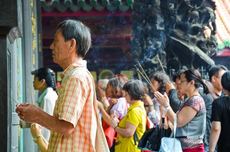Taipei Taiwan - Maj 13th 2017: Äldre asiatisk man med buddistiska rökelsepinnar som ber i den Longshan templet Religiös ritual, c arkivbild
