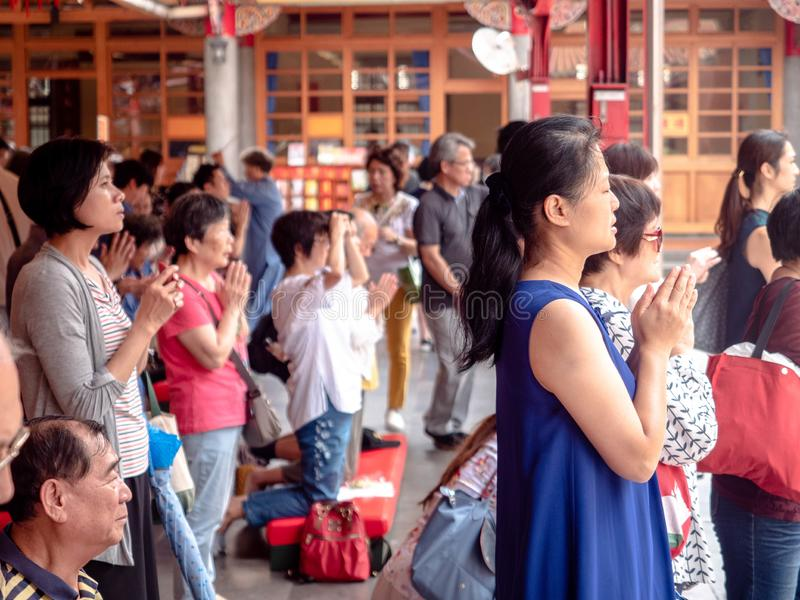 Taipei, Taiwan - May 13, 2019: People Asian with Buddhist incense sticks praying in Longshan Temple. Religious ritual, ceremony. Prayer. Concept religion royalty free stock photography